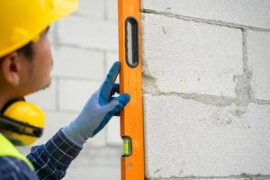 abgeschnittener Schuss eines Bauarbeiters, der Niveau auf Ziegelmauer prüft foto