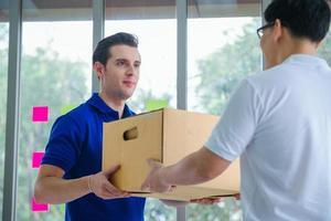Zusteller, der dem Kunden das Paket übergibt foto