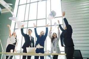 Geschäftsleute aufgeregt glückliches Lächeln, Gruppe von selbstbewussten Geschäftsleuten, die Papier in die Luft werfen, während sie hinter der Glaswand arbeiten, Erfolgsteamkonzept. foto
