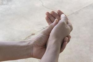Person, die unter Schmerzen am Handgelenk leidet foto