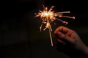 weibliche Hand, die einen brennenden Wunderkerzen-, Weihnachts- und Neujahrs-Wunderkerzenfeiertagshintergrund hält
