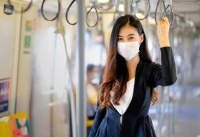junge Frau, die Himmelzug zur Arbeit nimmt foto