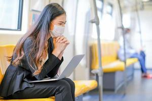 junge Geschäftsfrau, die eine Gesichtsmaske im Zug trägt foto