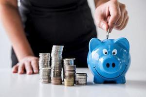 Person, die Geld in Sparschwein steckt foto