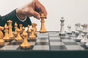 Schachbrett mit der Hand, die eine Schachfigur bewegt