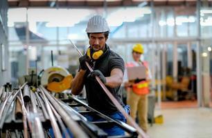 Techniker, der Kupferrohr am industriellen Arbeitsplatz hält foto