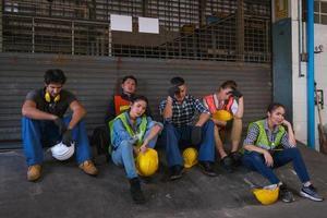 Eine Gruppe junger Industrietechniker macht eine Pause außerhalb der Arbeit.