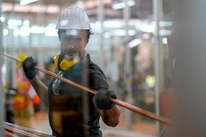 Techniker, der ein Kupferrohr am Fabrikarbeitsplatz hält