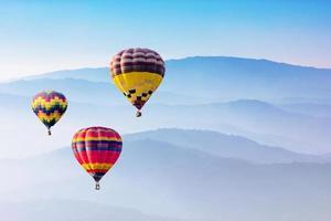 Heißluftballons fliegen über Berge foto