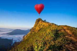 Herzförmiger Heißluftballon fliegt über einen Berg foto