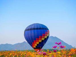 Heißluftballon landet im Feld der Blumen foto
