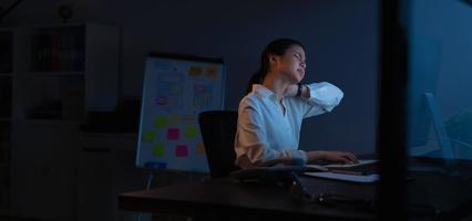 Frau hat Nackenschmerzen am Computer sitzen foto