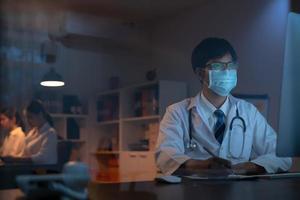 männlicher Arzt, der Maske trägt, die am Computer arbeitet foto