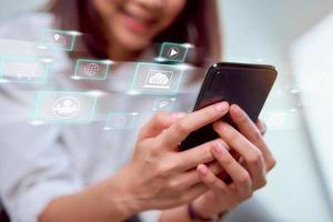 Frau hält Smartphone mit Social-Media-Symbolen angezeigt foto