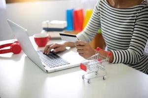 Frau sitzt am Computer online einkaufen foto
