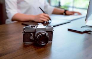 Filmkamera auf dem Schreibtisch mit Frau, die Fotos bearbeitet