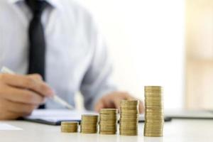 Stapel von Münzen auf Schreibtisch mit Geschäftsmann, der im Hintergrund arbeitet foto