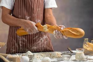 Chefkoch zieht frisches Brot in der Küche auseinander foto