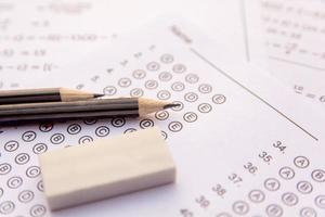 Nahaufnahme von Stiften und Radiergummi auf Testblättern