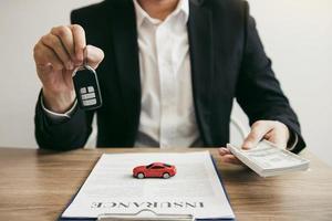 Autoverkäufer, der dem Kunden Schlüssel und Geld übergibt