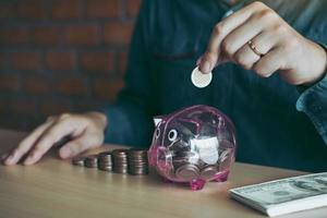 Nahaufnahme einer Hand, die Geld in Sparschwein legt foto