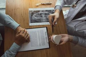 Zahnarzt erklärt dem Patienten den Pflegeplan foto