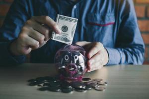 Mann, der Geld in Sparschwein steckt foto