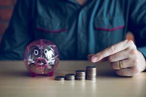 Mann stapelt Münzen neben Sparschwein foto