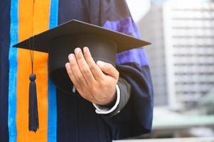 Nahaufnahme des Absolventen, der Abschlusskappe hält
