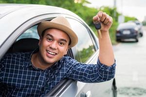 Mann hält Autoschlüssel vom Autofenster foto