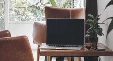 Laptop mit Espresso und Telefon im Wohnzimmer