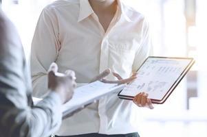 Zwei Geschäftsleute diskutieren mit dem Tablet über den Geschäftsplan foto