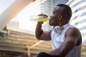 Mann, der abgefülltes Sportgetränk trinkt foto
