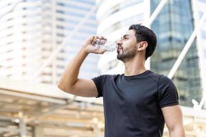 Mann trinkt Wasser in Flaschen