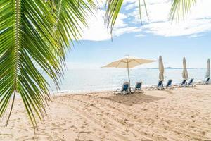 tropische Strandszene mit offenem Regenschirm foto