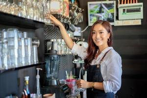 weiblicher asiatischer Barista, der lächelt, während er Kaffeemaschine benutzt