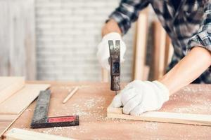 Mann hämmert Nagel in Holz foto