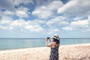 Frau, die am Strand fotografiert foto