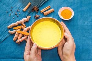 Hände halten goldene Milch oder Kurkuma Latte mit Zutaten
