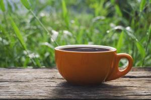 orange Tasse Kaffee auf dem Tisch draußen