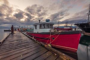 rotes und weißes Boot auf Dock unter bewölktem Himmel