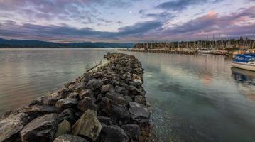 graue Felsen nahe dem Gewässer unter blauem Himmel foto