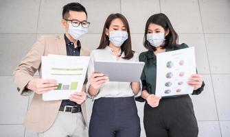 asiatische Geschäftsleute, die Gesichtsmasken tragen foto