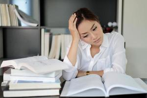 asiatische Geschäftsfrau, die Buch mit Hand auf Kopf liest