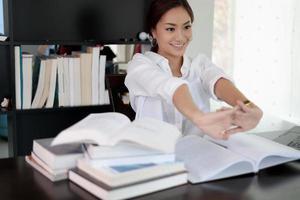 asiatische Frau, die sich im Büro ausdehnt und lächelt foto