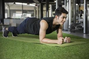 Mann in Yoga Plank Pose im Fitnessstudio foto