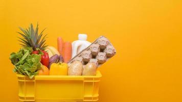 Schachtel mit Lebensmitteln auf gelbem Hintergrund