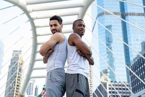 zwei Männer in Sportkleidung Rücken an Rücken stehend
