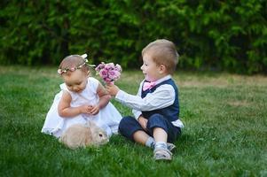 Junge gibt jungem Mädchen einen Blumenstrauß