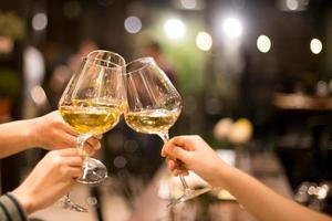 Freunde rösten mit Gläsern Wein